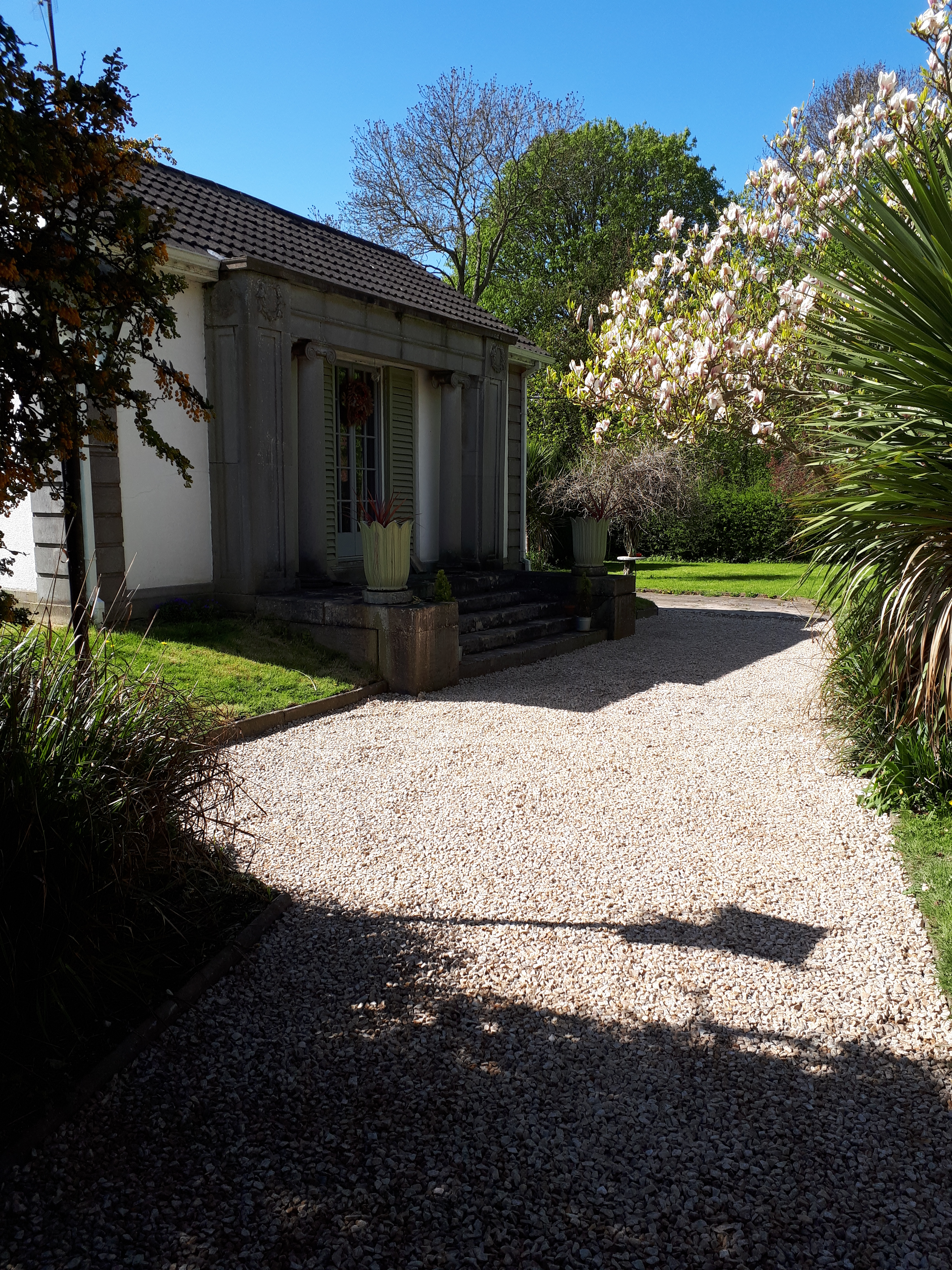 Image of a gravel driveway in a complementary garden stetting.