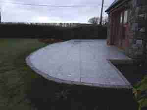 Image of curved silver granite patio with granite cobble edging