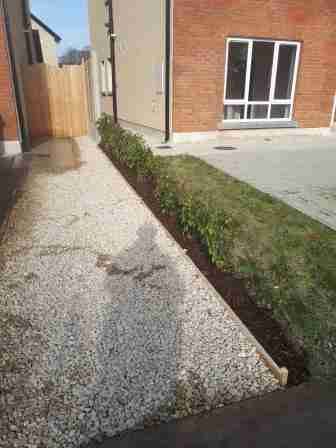 Image of the front garden with lawn removed and decorative gravel with timber edging and bark mulch beneath the hedge.
