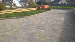 Image of new driveway block paved, and raised turf lawn Front garden design