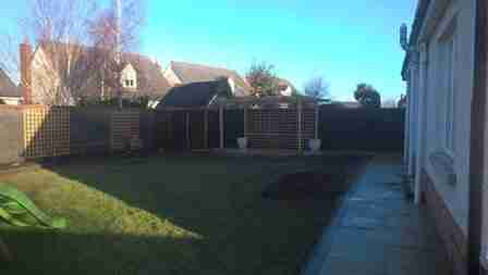 Photo of curved yellow limestone patio, pergola and raised beds