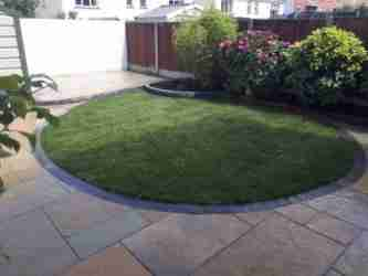 Image of a Curved turf lawn and yellow limestone paving