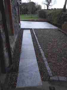 Image of silver granite path with gravel edging and silver granite retaining kerbs and cobbles