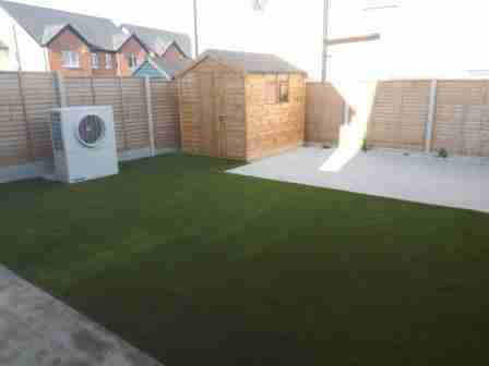Image of low maintenance garden with artificial lawn and silver granite textured patio slabs
