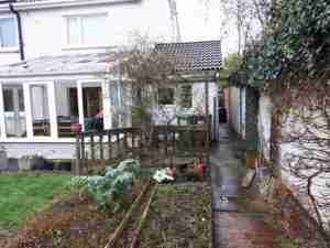 Image of garden before with old pergola and decking and beds