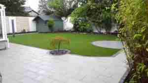 Image of redesigned garden with artificial lawn and silver granite paving and Japanese maple tree in gravel and brick edging