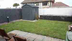 Image of th enew garden with raised beds, bollard lighting turf lawn and brick and gravel edging