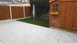 Image of newly designed garden space with artificial lawn and silver granite textured paving