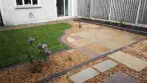 Image of lawn,New Limestone curved patio with cobble insets and plants