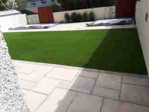 Concrete pads for steel sheds installed with paving and artificial lawn