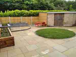 Yellow limestone paving, raised beds & turf lawn and new fecning