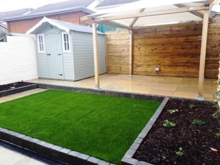Artificial lawn , Yellow limestone paving, raised beds, stepped garden
