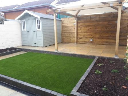 Stepped garden showing,Image of artificial lawn, yellow limestone paving and patio, raised beds, trellis and painted wall, Blue painted garden shed